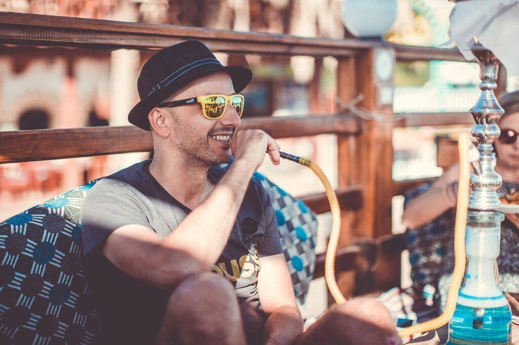 chico fumando cachimba con gafas de sol estando de fiesta